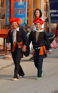 Two women from the Red Dao hilltribe, in traditional garb, walk down the central street in Sa Pa Village. The red headscarves are a characteristic feature.