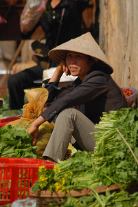 Street vendor sitting outside the produce market, selling home-grown vegetables and greens.