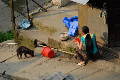 A woman sitting outside her home, feeding a stray puppy.