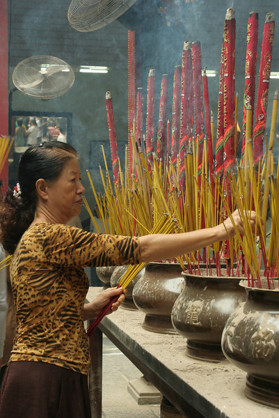 Making an offering at the pagoda, Saigon, Vietnam