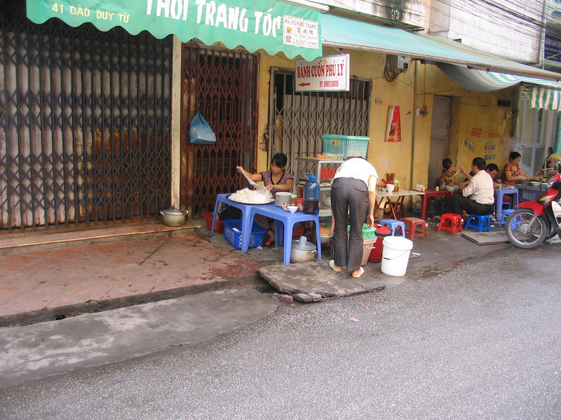 This woman is making noodles. Much of Vietnamese life is spent outside on the sidewalk.