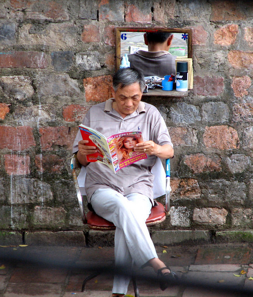A street barber on the outside wall of the Temple of Lit.