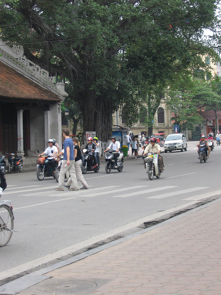 This is how you cross the road in Vietnam (although not usually in a crosswalk) just step into the madness, look straight ahead and walk slow.