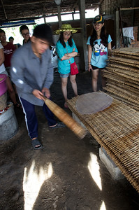 "A long narrow stick is used to lift and transfer the cooked rice sheet to a cooling ""rack"" (at far left corner)"