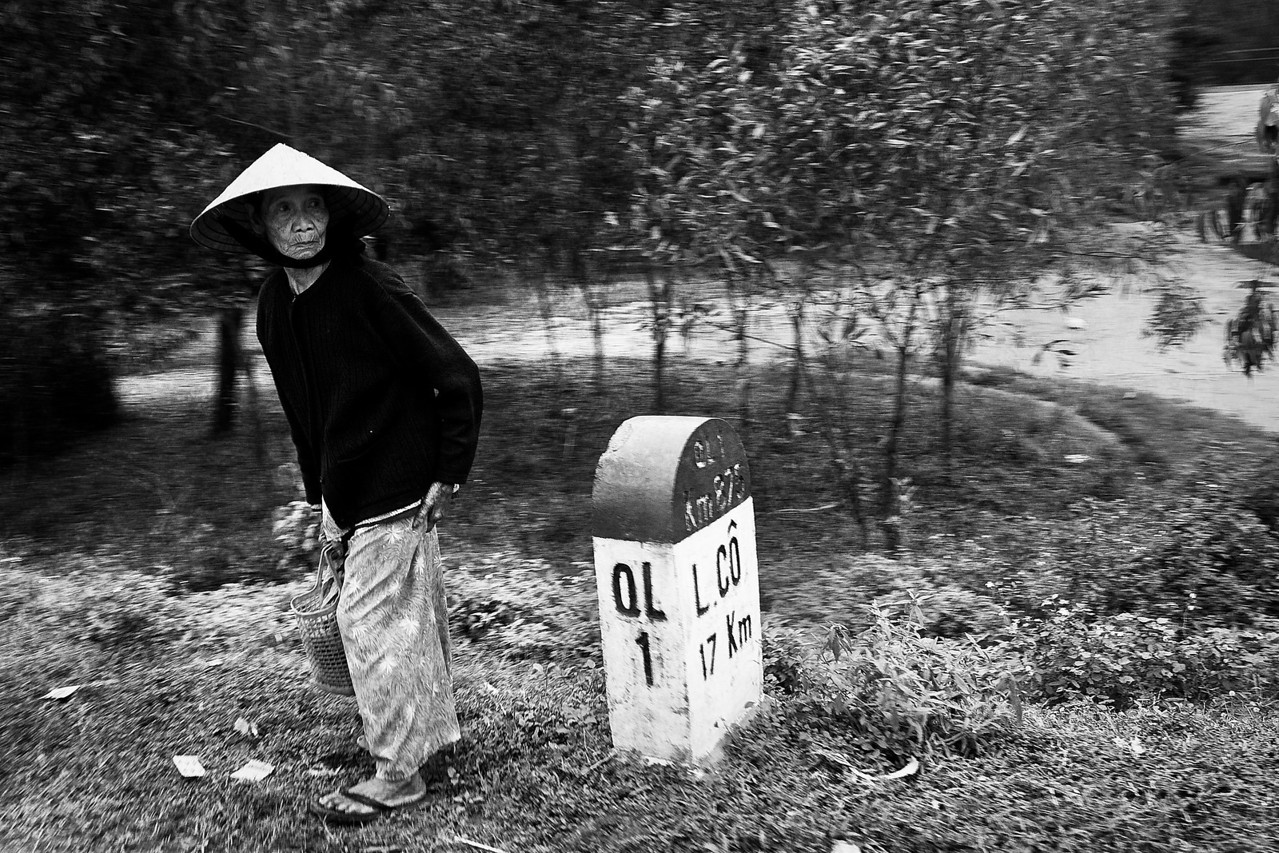 On the road to Danang, a woman looks for an opportunity to cross.
