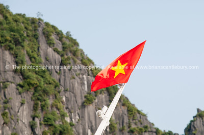 Flag of Vietnam against a wall of a Halong Bay Islet. Vietnam travel images and stock photos.