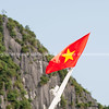 Flag of Vietnam against a wall of a Halong Bay Islet.<br /> Vietnam travel images and stock photos.
