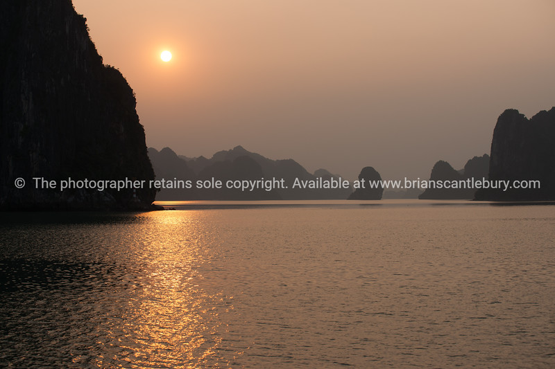 """Halong Bay setting sun.<br />  """"Descending dragon bay"""" is a UNESCO World Heritage Site, Vietnam travel images and stock photos."""