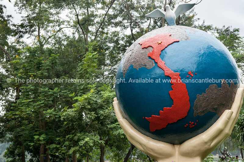 Sculptural Map of Vietnam on globe symbolically held up by two hands in the park along side Hoan Kiem Lake in Hanoi.