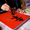 "Calligrapher in the Jade Mountain Temple, across the Sunbeam Bridge in Hoan Kiem Lake, Hanoi.  the Calligrapher is writing:  ""Happiness"" in Chinese script."