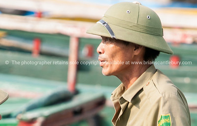 Halong Bay boatman in khaki and pith helmet. Vietnam travel images and stock photos.