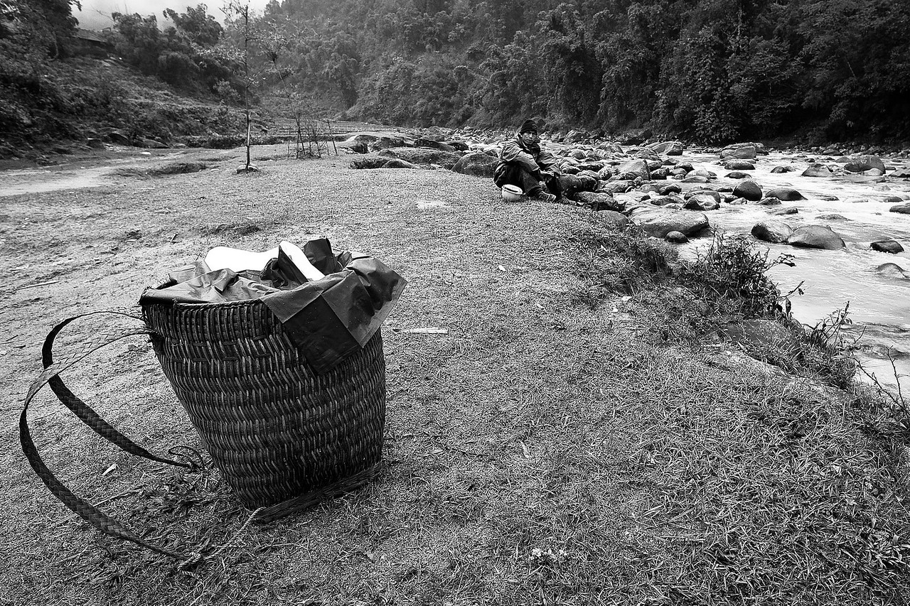 A Sapa Valley laborer rests by the river.