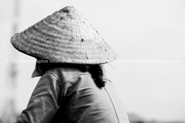 Black and white, woman in coolie hat from back. Vietnam travel images and stock photos.