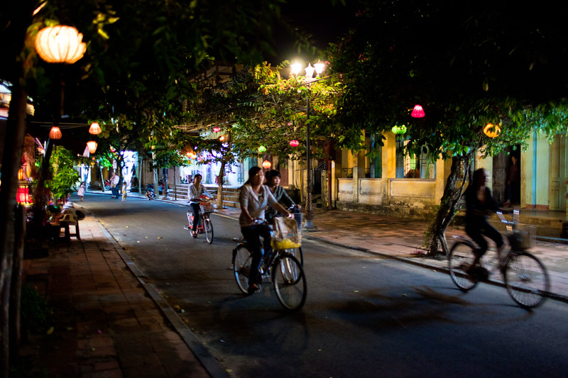 Locals ride through the ancient town in Hoi An - this area is closed to motorised traffic in the evenings.
