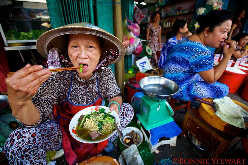 Market lady eating Pho