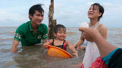 Family harvesting (small) seashells for sale to nearby restaurants