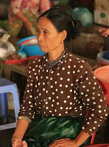 Serieuze dame op de markt van Hoi An. Hoi An, Vietnam.