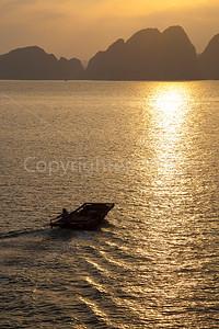Boat heading toward sunset in Ha Long Bay