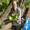 Happy man holding bunch of bananas in Mekong floating markets.