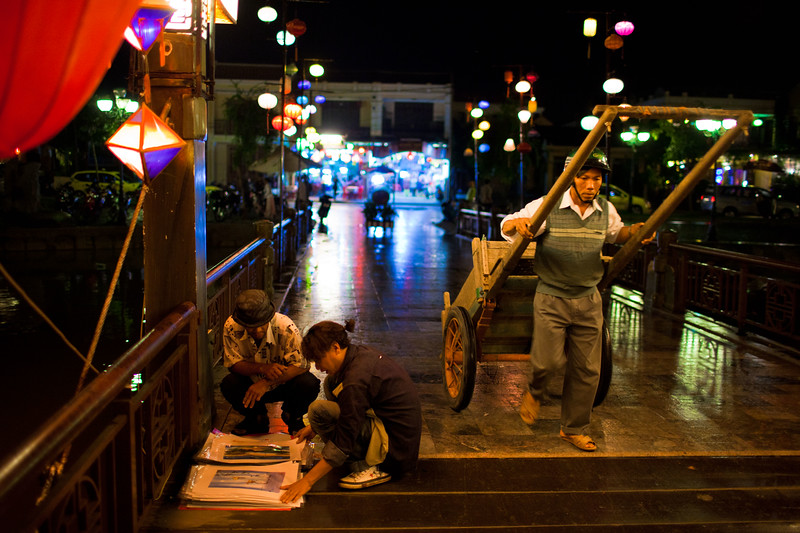 A man pulls a cart across a bridge in Hoi An while a local artist shows his work to a passer-by.