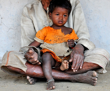 Young girl in her grandfather's lap at their village. Villages in rural India in the state of Maharashtra.