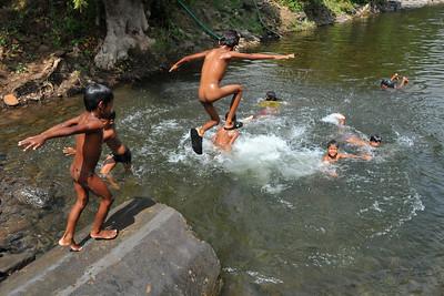 You children bathing and having fun in an open water body in rural Maharashtra.