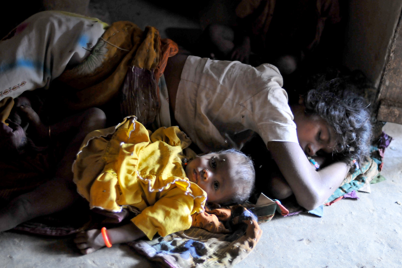 Unwell young mother still breast feeding her young baby girl. Villages in rural India in the state of Maharashtra.