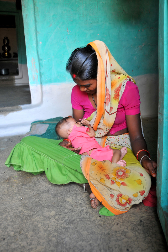 Young mother breast-feeding her baby boy in her village.