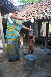 Mother giving her daughter a bath. Bathing in a village. Villages in rural India in the state of Maharashtra.