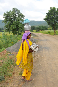 Women carry pots on their head in rural India.