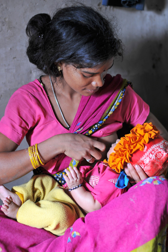 Young mother breast-feeding her baby at her village home.<br /> Villages in rural India in the state of Maharashtra.