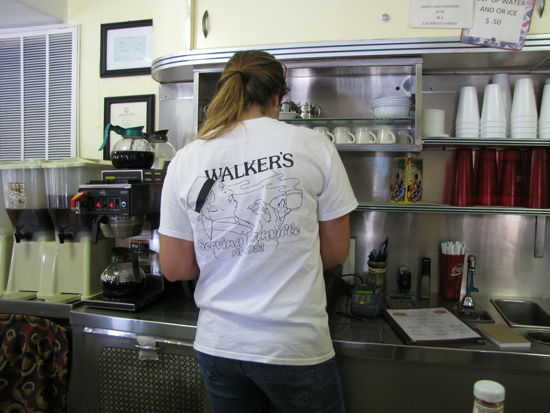 "Our Waitress at Walker's Diner (""Serving Farmville Since 1952"")<br /> The saga begins in 1952, for that was when Allen Nance Fore (1911-1990) and Dr. Robert Jackson Martin, Jr. (1910-1988) teamed up and bought the property upon which the diner sits.  Allen Fore was a pharmacist and was the owner of Gray's Drug Store. Dr. Martin was head of the optical department at Martin the Jeweler's. When Dr. Martin died in 1988, Fore purchased Martin's undivided interest from the estate and became the sole owner of this lot.  In the spring of 1955, Paul T. O'Neil leased the lot. He then placed an order on March 7, 1955, for ""One Master Model 15 Stool Valentine Steel Building"" with Valentine Manufacturing, Inc., of Wichita, Kansas. The cost of the diner was $5,000."