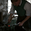 Frontier Culture Museum's 18th century Irish blacksmith shapes his glowing iron.