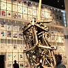 Twisted metal wreckage of the World Trade Center with a back drop of newspaper front page headlines from around the world.