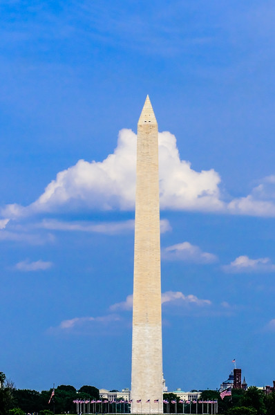 """Washington Monument - View of the Monument and its circle of flags from the Lincoln Memorial side of the Mall.  The Smithsonian """"Castle"""" is to the right and the US Capitol is directly behind the obelisk."""