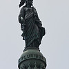 "The bronze Statue of Freedom by Thomas Crawford is the crowning feature of the dome of the United States Capitol. The statue is a classical female figure of Freedom wearing flowing draperies. Her right hand rests upon the hilt of a sheathed sword; her left holds a laurel wreath of victory and the shield of the United States with thirteen stripes. Her helmet is encircled by stars and features a crest composed of an eagle's head, feathers, and talons, a reference to the costume of Native Americans. A brooch inscribed ""U.S."" secures her fringed robes. She stands on a cast-iron globe encircled with the national motto, E Pluribus Unum. The lower part of the base is decorated with fasces and wreaths. Ten bronze points tipped with platinum are attached to her headdress, shoulders, and shield for protection from lightning. The bronze statue stands 19 feet 6 inches tall and weighs approximately 15,000 pounds. Her crest rises 288 feet above the east front plaza.<br /> <br /> A monumental statue for the top of the national Capitol appeared in Architect Thomas U. Walter's original drawing for the new cast-iron dome, which was authorized in 1855. Walter's drawing showed the outline of a statue representing Liberty; Crawford proposed an allegorical figure of ""Freedom triumphant in War and Peace."" After Secretary of War Jefferson Davis objected to the sculptor's intention to include a liberty cap, the symbol of freed slaves, Crawford replaced it with a crested Roman helmet.<br /> <br /> Crawford was commissioned to design the Statue of Freedom in 1855 and executed the plaster model for the statue in his studio in Rome. He died in 1857 before the model left his studio. The model, packed into six crates, was shipped from Italy in a small sailing vessel in the spring of 1858. During the voyage the ship began to leak and stopped in Gibraltar for repairs. After leaving Gibraltar, the ship began leaking again to the point that it could go no farther than Bermuda, where the model was stored until other transportation could be arranged. Half of the crates finally arrived in New York in December, but all sections were not in Washington until late March of 1859.<br /> <br /> Beginning in 1860, the statue was cast in five main sections by Clark Mills, whose bronze foundry was located on the outskirts of Washington. Work was halted in 1861 because of the Civil War, but by the end of 1862 the statue was finished and temporarily displayed on the Capitol grounds. The cost of the statue, exclusive of installation, was $23,796.82. Late in 1863, construction of the dome was sufficiently advanced for the installation of the statue, which was hoisted in sections and assembled atop the cast-iron pedestal. The final section, the figure's head and shoulders, was raised on December 2, 1863, to a salute of 35 guns answered by the guns of the 12 forts around Washington.<br /> <br /> The plaster model of the statue, which had been in storage for 25 years, was reassembled and restored in the basement rotunda of the Russell Senate Office Building, where it was returned to permanent public display in January 1993.<br /> <br /> On May 9, 1993, after almost 130 years in place, the bronze statue was removed from its pedestal by helicopter for restoration. The work was needed because of extensive pitting and corrosion on the surface of the bronze and because of a crack and rusting on the cast-iron pedestal. The project was guided by the recommendations of a thorough conservation and engineering study conducted in 1991. The United States Capitol Preservation Commission provided $780,000 in privately raised funds, which covered all project costs.<br /> <br /> The disfiguring caulk and much of the corrosion were removed by water blasted at medium pressure. Repairs to the statue included the insertion of over 700 bronze plugs in the most significant pits; bronze patches were also inserted where needed. Rusting original iron elements and the interior paint were removed. The bronze, which varied in composition and condition, was painstakingly repatinated to the ""bronze green"" noted in early records. Finally, layers of acrylic lacquer and wax were applied to protect the surface against further corrosion, and small gaps were sealed with caulk.<br /> <br /> The cast-iron pedestal was restored in place atop the dome. The metal was stripped of paint, and the wreaths and fasces were removed to ensure that they were thoroughly cleaned and coated. The crack was permanently repaired, and the entire pedestal was primed and painted with a color specially mixed to match the statue.<br /> <br /> Restoration of the statue and the pedestal was completed in approximately four months. The Statue of Freedom was returned to its pedestal by helicopter on October 23, 1993, amidst the congressional celebration of the bicentennial of the U.S. Capitol.<br /> <br /> Freedom is scheduled to undergo maintenance every two years; this will include inspection, cleaning, and waxing to ensure continued preservation of the bronze."