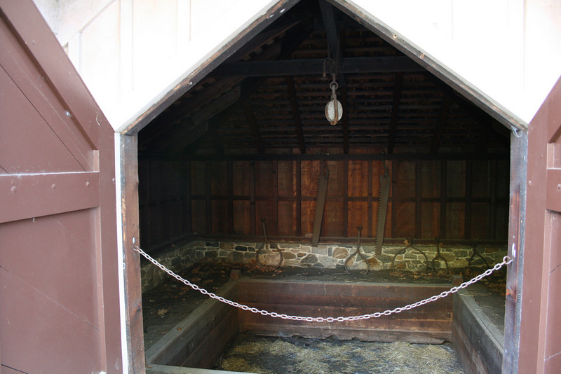 This is the inside of the smokehouse. Notice the hook for hanging the meat and the pit for doing the smoking.