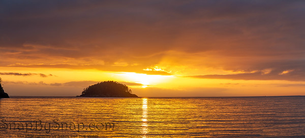 Small island in silhouette panorama against a brilliant sunset and lots of colorful reflections