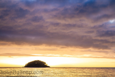 Small island in silhouette against a brilliant sunset and lots of colorful reflections