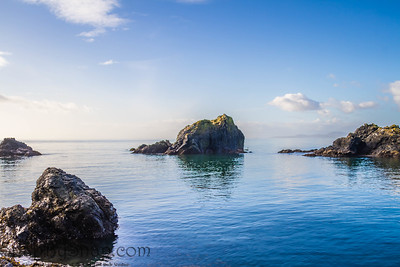 Rocks protruding from the surrounding blue ocean