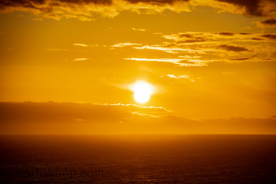 The golden sun setting on the ocean horizon with clouds and haze