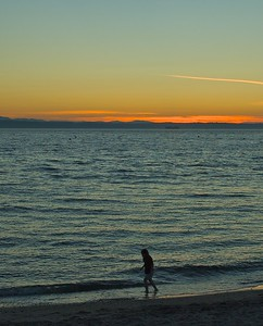 Child walking along the Edmonds waterfront beach at sunset.