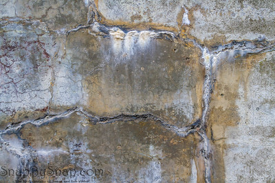 Concrete wall that is heavily cracked with age
