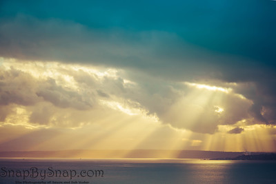 A dramatic sunset through the clouds over the ocean with rays of light