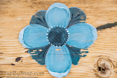 A blue flower painted on wood