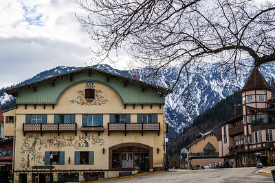 Bauernhaus style Bavarian buildings with snow covered mountains in the distance