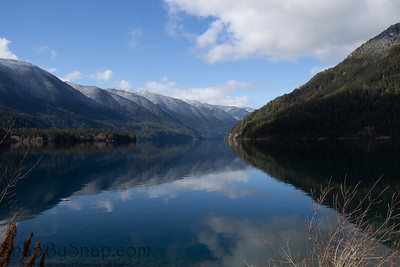 A mountain lake on a bright sunny day with blue skies and snow dusting the top of the mountains