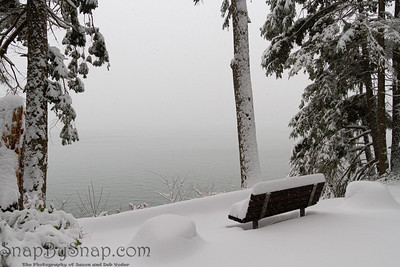 A single snow covered bench looking out over the water