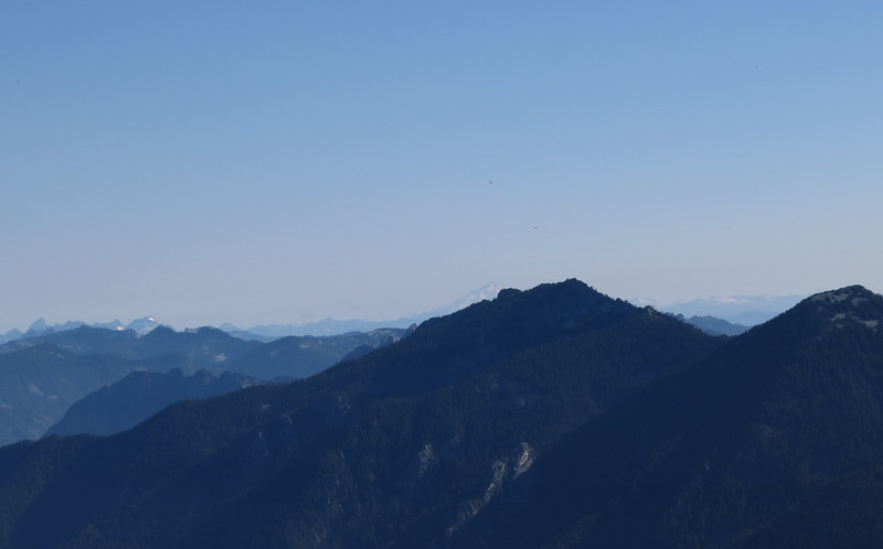 Looking north, that's Glacier Peak (50 miles away) peeking from behind Preacher Mountain.