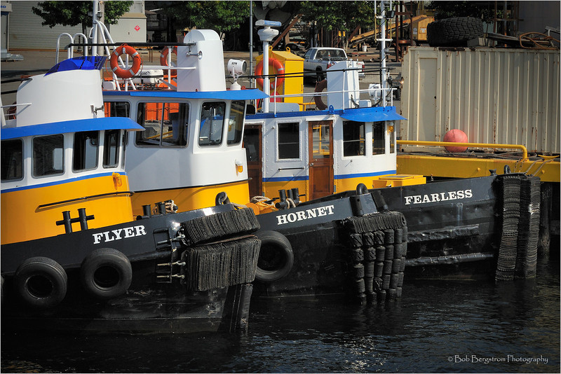 Three smaller tugboats lined up at the dock.